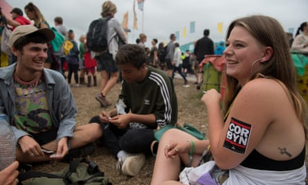 A young woman wears a Jeremy Corbyn sticker on her arm at Glastonbury festival.