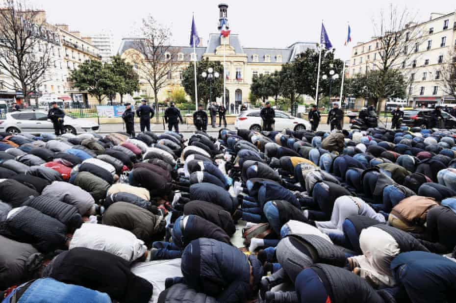 French protest … Muslim men pray in the street after their mosque is closed in Clichy in March 2017.