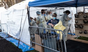 Medical workers don protective equipment at the beginning of their shift at the emergency field hospital.