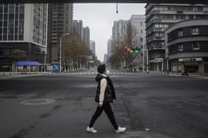 A woman walks on an empty road on 27 January when Wuhan was under strict lockdown.