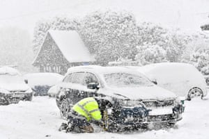 A man fits snow chains to his car in Brenchley in Kent