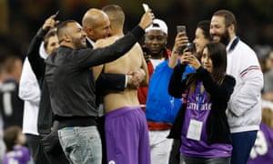 Real Madrid coach Zinedine Zidane celebrates with Karim Benzema as people take selfies around them.