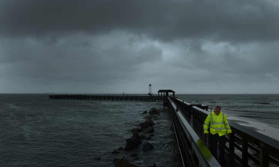 A Cape Charles police officer walks back to his vehicle after checking out the fishing pier in Virginia on Saturday as the storm intensified along the Atlantic coast.
