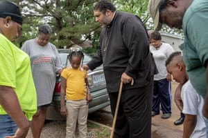 TCHULA, MS - May 9, 2019: Rev. Dr. William Barber prays with Akeevia Carter, 7, her grandmother Harriett, sister Akeelah and mother Keywanna, while visiting Tchula residents whose homes have been affected by flooding. Andrea Morales for The Guardian