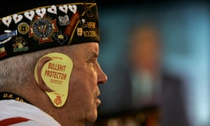 Bill Moyer, 73, wears 'bullshit protector' flaps over his ears while President George W Bush addresses veterans in Salt Lake City in 2005.
