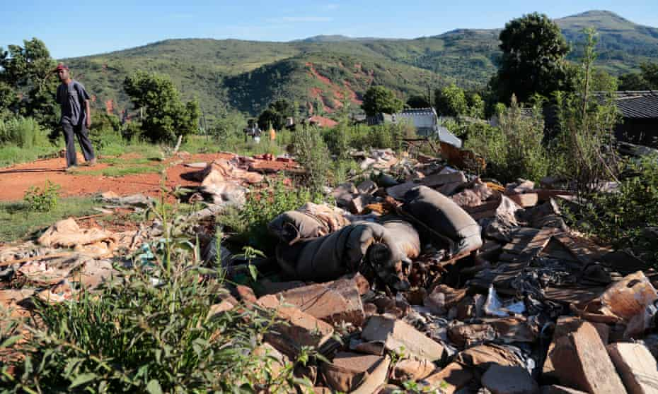 A man in Ngangu, Chimanimani, walks past debris from homes destroyed by Cyclone Idai