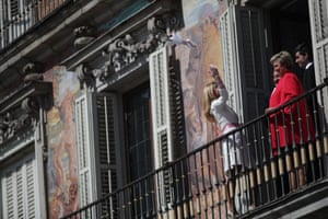 A woman throws the bouquet from a balcony in the Plaza Mayor after getting married