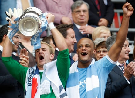 Manchester City's Joe Hart (L) lifts the FA Cup as Vincent Kompany celebrates winning the FA Cup final against Stoke City, in May 2011