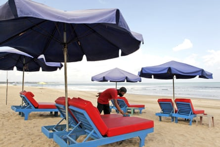 A worker cleans chairs for rent as beaches reopen in Bali.