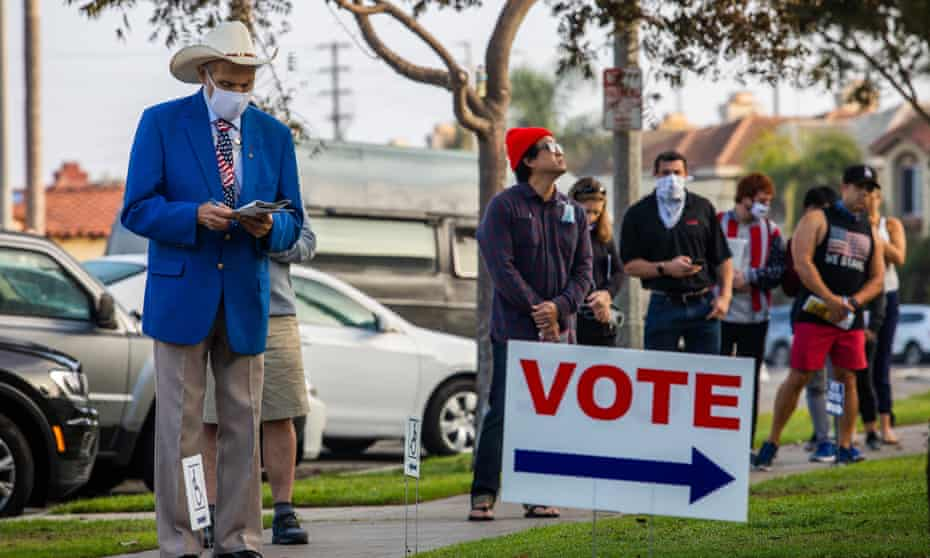 People stand in line to vote as the sun rises in Huntington Beach, California, on 3 November.