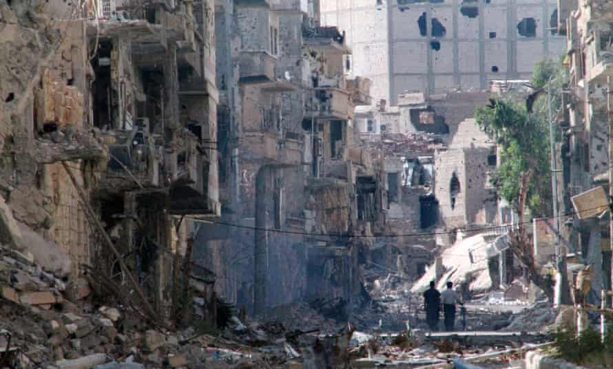 Syrians walk down a destroyed street Deir ez-Zor where Isis is accused of killing 85 civilians.