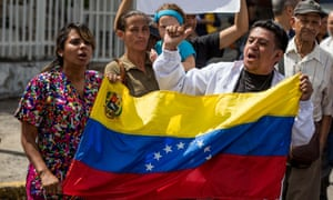 Hospital workers protest in Caracas. Many Venezuelans are struggling to find food and medicine.