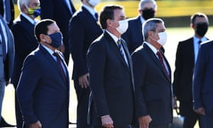 Jair Bolsonaro (C), his Vice-President Hamilton Mourao (L) and Chief of Staff Walter Souza Braga Netto (R) wear face masks as they attend the flag-raising ceremony before a ministerial meeting at the Alvorada Palace in Brasilia in May.