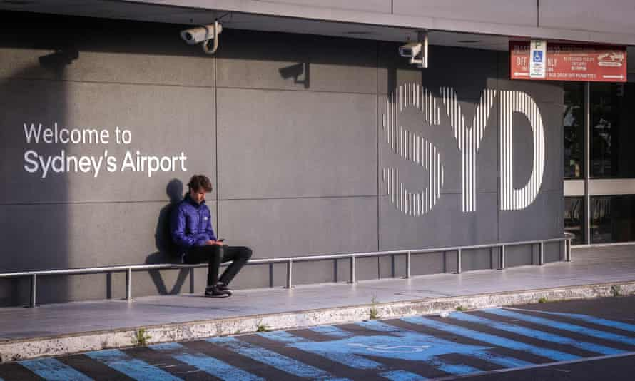 A man sits outside the departures area of the Sydney international airport. Rightwing group LibertyWorks has launched a federal court challenge to Australia's travel ban.