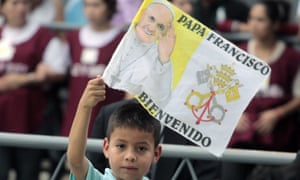 A child flutters a flag as faithful wait for Pope Francis outside the Metropolitan Cathedral in Asuncion on Saturday.