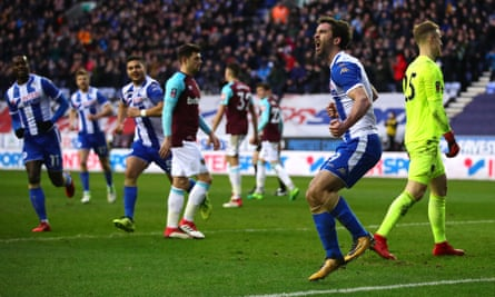 Will Grigg celebrates scoring Wigan's second goal with a penalty against West Ham.