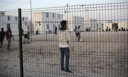 Young migrants play football near the shipping containers they are temporarily being housed in near Calais.