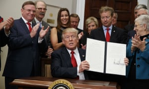 Donald Trump shows an executive order on healthcare that he signed in the Roosevelt Room of the White House in Washington.