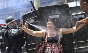 A Brazilian policeman sprays teargas at demonstrators during protest against delayed payments for public workers in Rio de Janeiro on Wednesday.