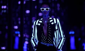 A model presents a creation from the Fall/Winter 2019/20 Women collection by Yves Saint Laurent during the Paris Fashion Week lit only by UV light