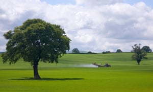 Farm tractor spraying insecticide on to green fields of English countryside
