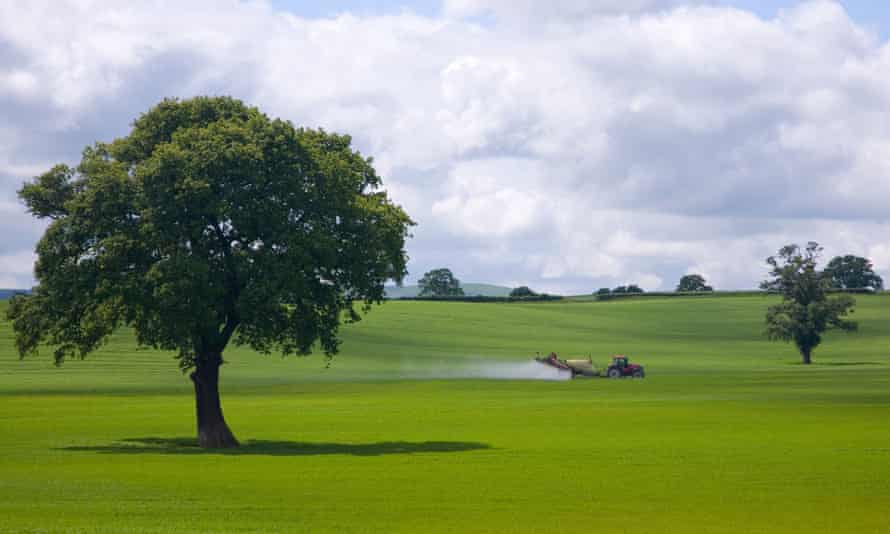 Farm tractor spraying insecticide on to green fields in England