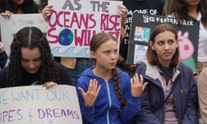Greta Thunberg, centre, pictured with activists outside the UN earlier this month, will address massed protesters at the climate strike in New York on Friday