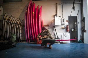 French surfer Justine Dupont waxes her board before heading out on the water.