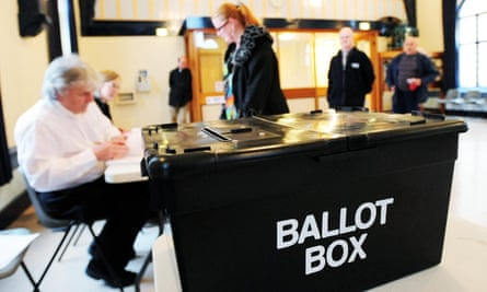 Workers at a UK ballot box