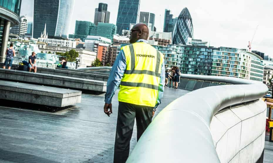 A security guard patrols on Queen's Walk, part of the More London development near London City Hall.