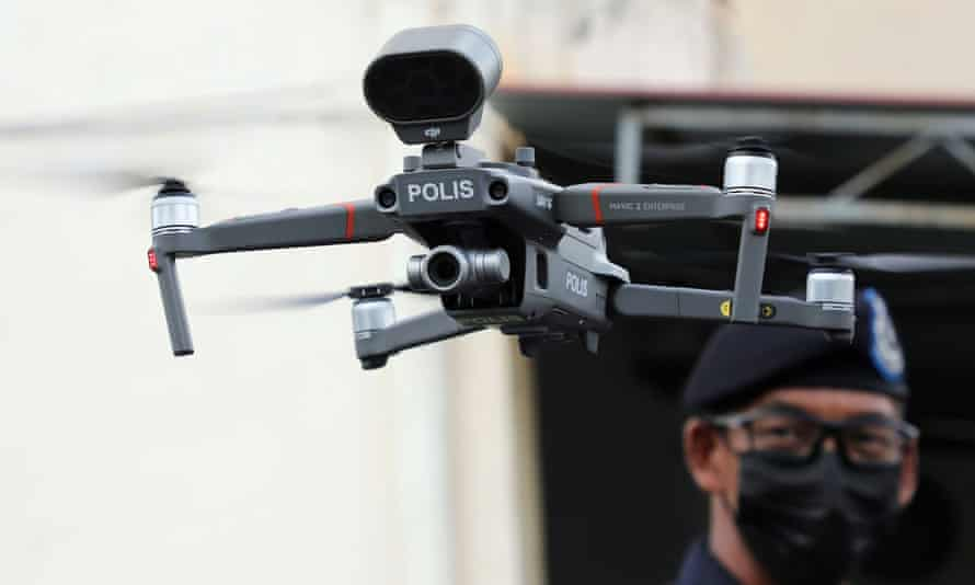 A police officer operates a drone to inspect the area under enhanced lockdown, amid the coronavirus disease (COVID-19) outbreak in Banting, Malaysia October 28, 2020.