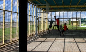 Children play basketball in a wire cage at Don Dale juvenile detention centre, Darwin Australia.