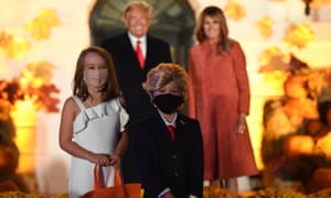 Children dressed as Donald and Melania Trump pose in front of the couple in Washington DC