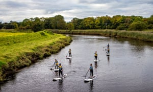 Six Girls paddleboarding on a river in Northern Ireland