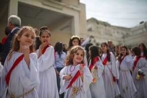 children in white dresses and red sashes