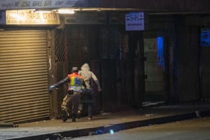 A police officer chases a man in Johannesburg who violated the lockdown order, on 27 March