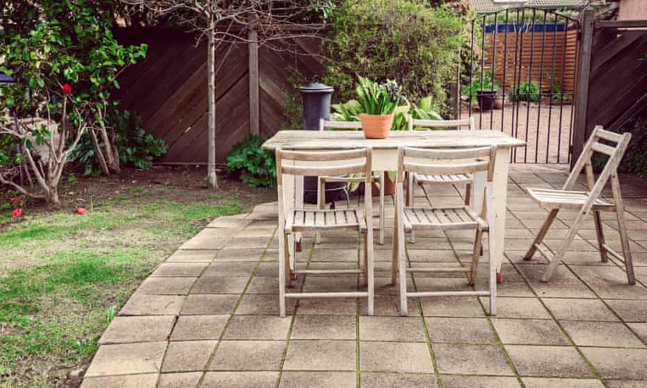 Vintage wooden table with flower in the pot placed in the garden