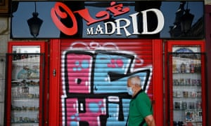 a man walks past a closed bar in Madrid
