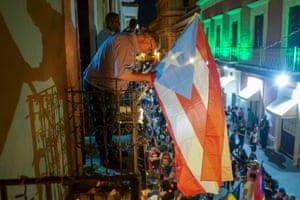 Alejandro Jeffs installs a Puerto Rican flag on his balcony.