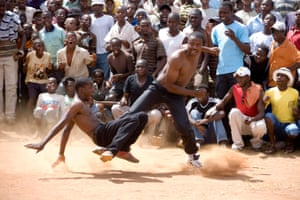 """Bareknuckle boxers excite the crowd with their dramatic fighting displays. - Local champions from the village of Gaba meet their counterparts from neighbouring Chifudzi village, in an annual bareknuckle boxing tournament known as the """"Musengwa"""". It is seen as a test of manhood, and is open to all who are considered brave enough to confront their fears, regardless of age, size or strength. Women are not allowed to attend. Venda, South Africa. 2008"""