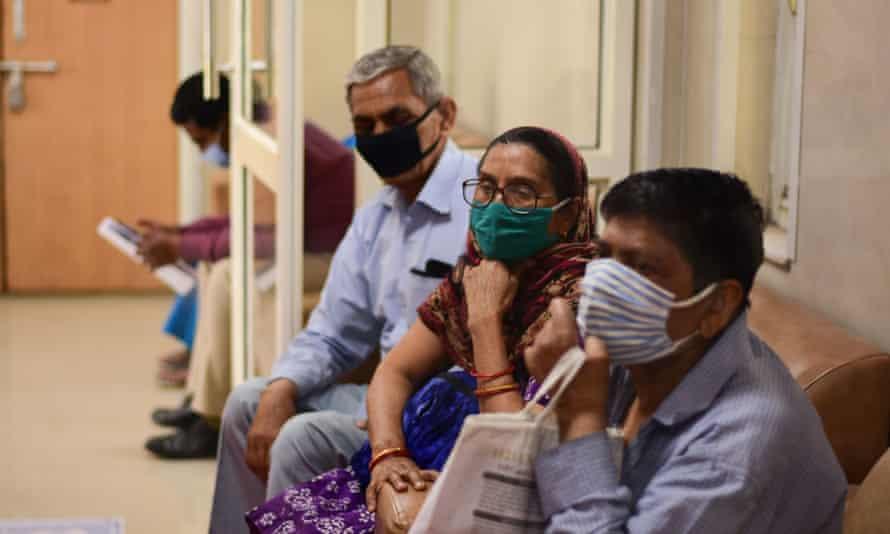 People wait for coronavirus vaccines in Delhi.