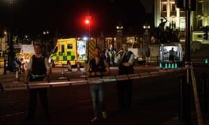 Ambulances and police emergency response teams work outside Buckingham Palace.