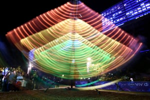 Children ride on an installation called Swing Glow.