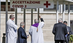 A priest blesses the entrance to the Columbus Covid 2 hospital, a new facility in Rome