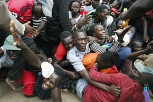 Nairobi, Kenya: residents of the Kibera slum desperate for food aid push through a gate causing a stampede that police dispersed with teargas