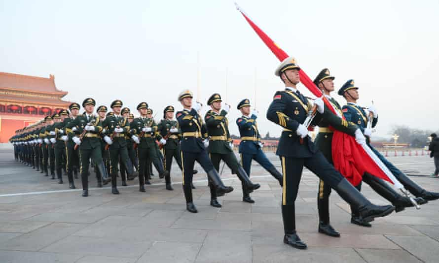 Chinese People's Liberation Army (PLA) members march to the flagpole during a flag-raising ceremony at the Tiananmen Square