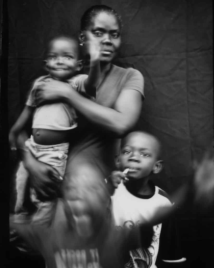 Marie Mirlande Caceus, from Haiti, poses for a portrait with her sons, Miguel and Lilliam, and a family friend, three-year-old Ryan, in Tijuana, Mexico. Rendered homeless by Hurricane Matthew, Caceus migrated to Brazil and then the US-Mexico border. She and her husband have decided not to cross into the States for fear of being deported back to Haiti. Caceus, who speaks Creole, is slowly learning Spanish, recently adding 'amigo', 'hola' and 'arroz' to her vocabulary