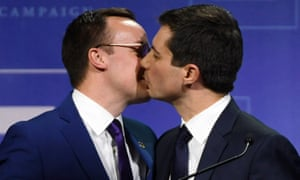 Pete Buttigieg kisses his husband, Chasten Glezman, on stage.