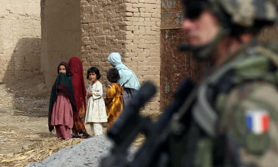 Afghan girls look at a French soldier in Showal town, Helmand, in 2010.