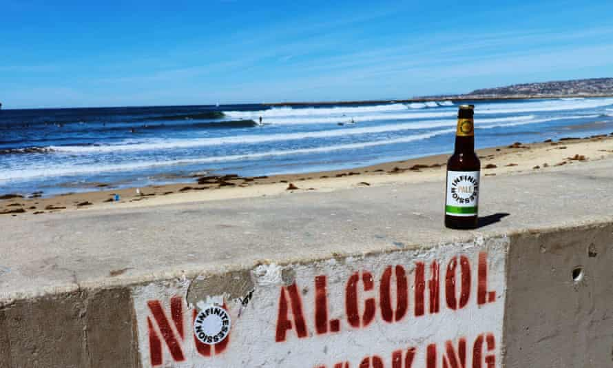 An Infinite Sessions beer on a 'no alcohol' sign by a beach.